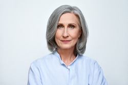 Confident beautiful mature business woman standing isolated on white background. Older senior businesswoman, 60s grey haired lady professional looking at camera, close up face headshot portrait.