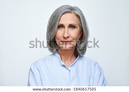 Confident beautiful mature business woman standing isolated on white background. Older senior businesswoman, 60s grey haired lady professional looking at camera, close up face headshot portrait. Zdjęcia stock ©
