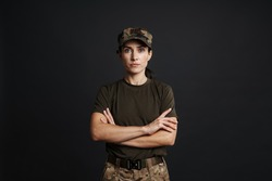 Confident beautiful soldier woman standing isolated over black background, arms folded