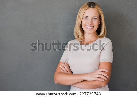 Confident beauty. Cheerful mature woman keeping arms crossed and smiling while standing against grey background