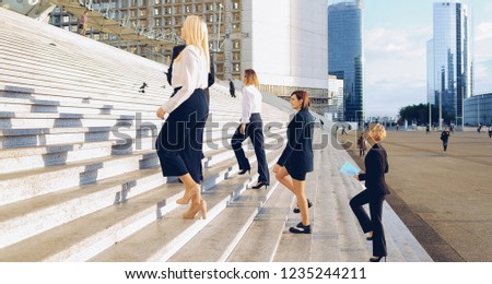 Confident biz members with boss going up stairs in La Defense Paris,  . Concept of official journey and foreign colleagues. Young successful people walking in shiny weather.