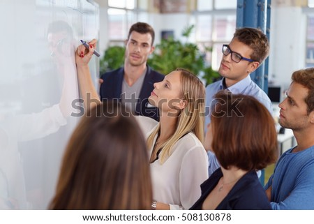 Confident blond woman writing on blank white board with fellow young adult workers standing around smiling