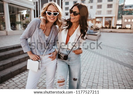 Confident blonde girl in sunglasses enjoying outdoor photoshoot with best friend. Stunning dark-haired female model embracing sister on the street.