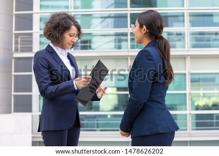 Confident boss and secretary standing on street. Cheerful young confident employees wearing formal suits transferring documents. Business confidence concept #1478626202