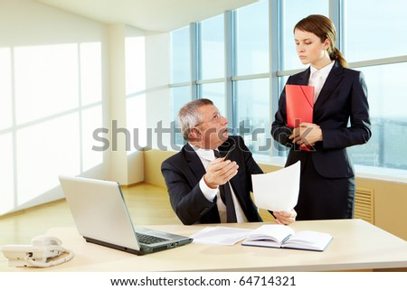 Confident boss with paper explaining something to secretary in the office