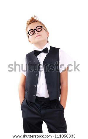 Confident boy in bow tie and suit looking up to the copy space area