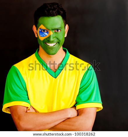 Confident Brazilian man with arms crossed and painted face