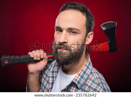 Confident, brutal bearded man with big axe on a red background.