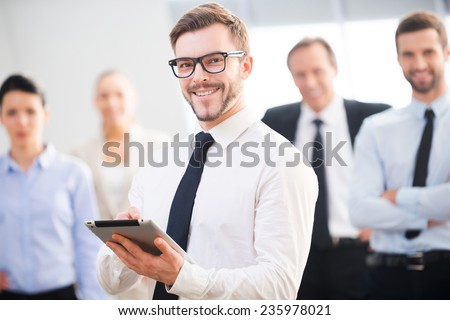 Confident business expert. Confident young businessman holding digital tablet and smiling while his colleagues standing in the background  #235978021