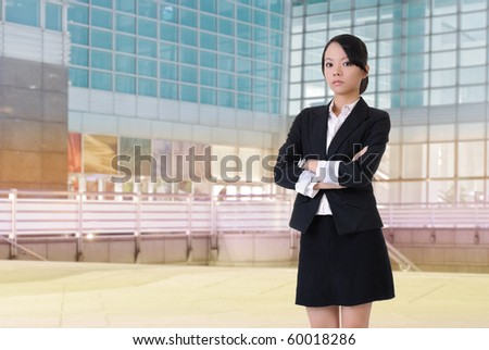 Confident business lady standing in front of colorful office building.