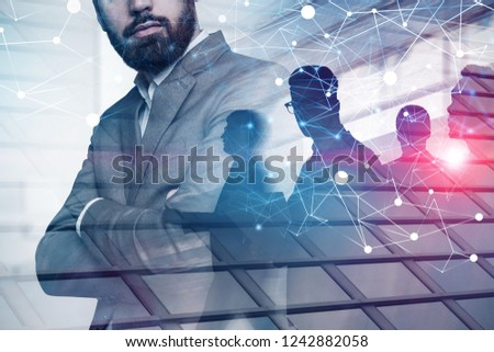 Confident business leader standing with crossed arms with his business team in the background with double exposure of network hologram. Toned image