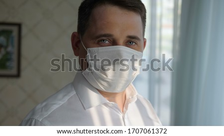 Confident business man in a medical mask at home looking to came