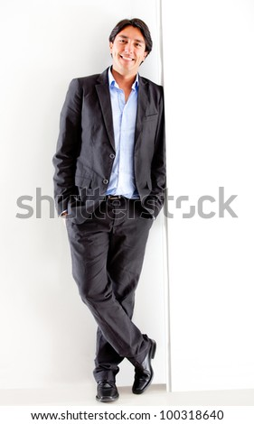 Confident business man leaning against the wall
