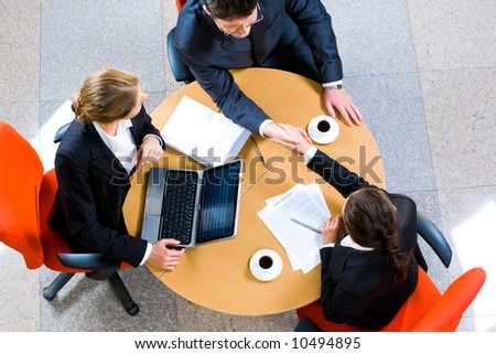 Confident business partners sitting at the table and shaking hands
