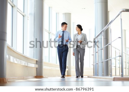 Confident business partners walking down in office building and talking #86796391