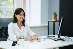 Confident Business Woman At Office Desk Working