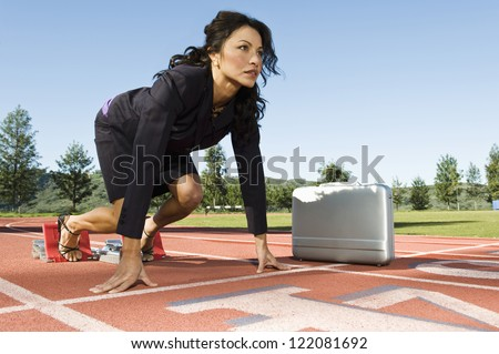 Confident business woman at start position of a racing track with briefcase against sky