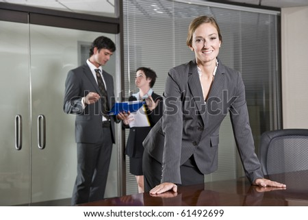 Confident business woman standing in boardroom, colleagues meeting in background