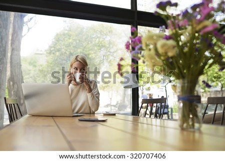 Confident business woman work on laptop computer holding the cup of cafe,female freelancer at distance work via net-book enjoying her cup of tea,young caucasian student learning on-line at coffee shop