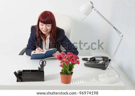 Confident business woman writes in her diary