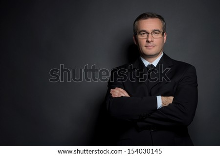 Confident Businessman. Confident Middle-Age Man In Formalwear Keeping His Arms Crossed And Looking At Camera While Standing Isolated On Grey
