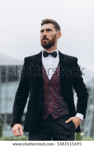 Confident businessman. Confident young man in full suit adjusting his sleeve and looking away while standing outdoors with cityscape in the background