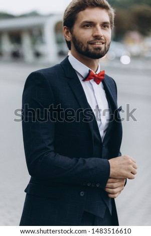 Confident businessman. Confident young man in full suit adjusting his sleeve and looking away while standing outdoors with cityscape in the background #1483516610