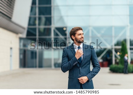Confident businessman. Confident young man in full suit adjusting his sleeve and looking away while standing outdoors with cityscape in the background #1485790985