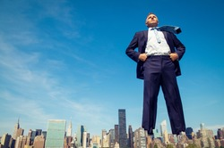 Confident businessman giant standing with hands on hips above the city skyline