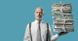 Confident businessman holding a pile of paperwork effortlessly with one hand, easy business administraton concept