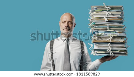 Confident businessman holding a pile of paperwork effortlessly with one hand, easy business administraton concept Stock photo ©