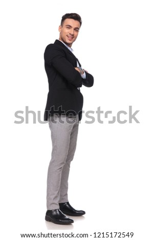 confident businessman in black suit smiling and waiting in line while standing on white background with arms folded, full length picture #1215172549