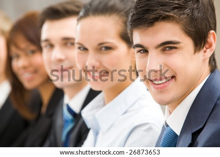 Confident businessman looking at camera at background of his colleagues