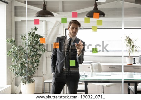 Confident businessman looking at glass wall with colorful sticky papers in office, executive manager team leader working on corporate project plan or strategy, reading notes on tasks on stickers Photo stock ©