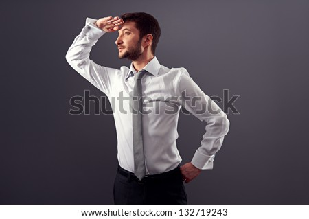 confident businessman looking into the distance. studio shot over dark background