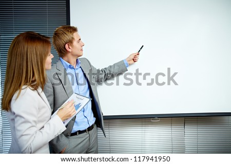Confident businessman pointing at whiteboard while making speech with smart secretary near by