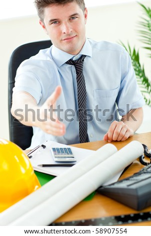 Confident businessman reaching his hand to the camera in his office
