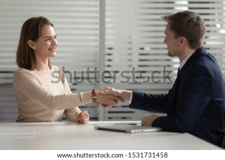 Confident businessman shaking hand of smiling businesswoman in office, good negotiation, recruiter handshaking with smiling female candidate, hiring process, successful job interview concept