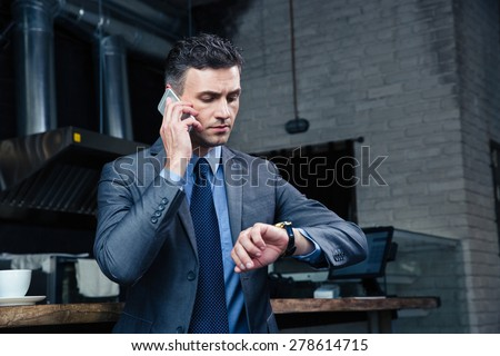 Confident businessman speaking on the phone and looking on the wristwatch in cafe Stockfoto ©