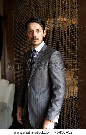 confident businessman standing against tiled wall