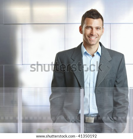Confident businessman standing in modern office with glass and metal walls, smiling.