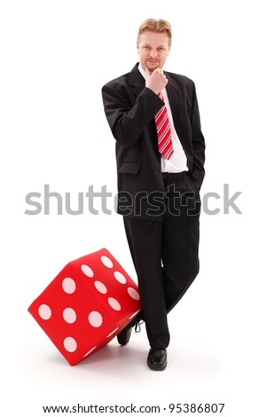 Confident businessman standing near big red dice