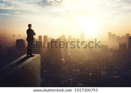 Confident businessman standing on the building rooftop while looking at the silhouette of cityscape at dusk time