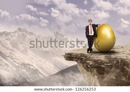 Confident businessman standing on top of a mountain beside golden egg
