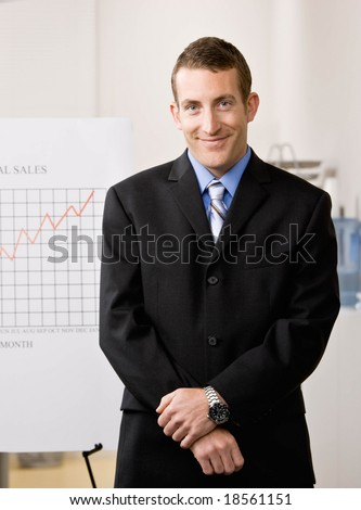 Confident businessman standing with financial analysis chart