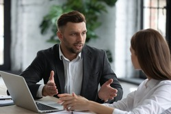 Confident businessman talking with young attractive businesswoman in boardroom at meeting. Leader presenting new business concept for focused female colleague discuss. Team together using laptop.