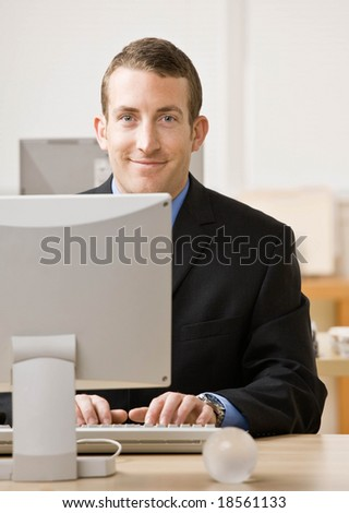 Confident businessman typing on computer at desk