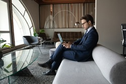 Confident businessman using laptop, sitting on couch in modern office, successful executive entrepreneur wearing glasses and suit working on project, searching, analyzing information, financial stats