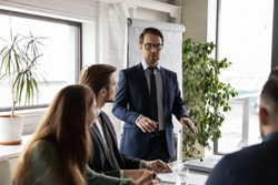 Confident businessman wearing glasses making flip chart presentation in boardroom, mentor coach explaining project strategy or marketing plan, executive leading corporate meeting, briefing