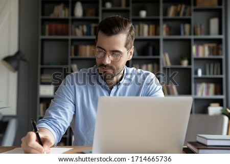 Confident businessman wearing glasses writing notes or financial report, sitting at desk with laptop, focused serious man working with paper documents, student studying online, research work